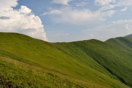 Mountain ridge slopes covered by green grass and cloudy blue sky photo
