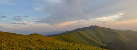 Light blue evening sky above grassy mountain ridge panorama photo