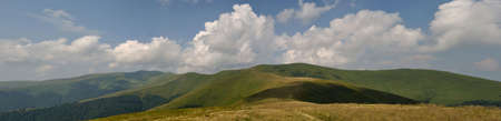 White summer clouds above Carpathian mountain meadows panorama photo