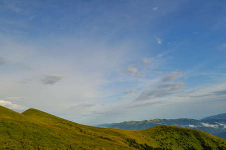 Cloudy blue sky upon green mountains photo