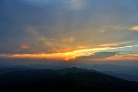 Setting sun shining over blue mountains photo