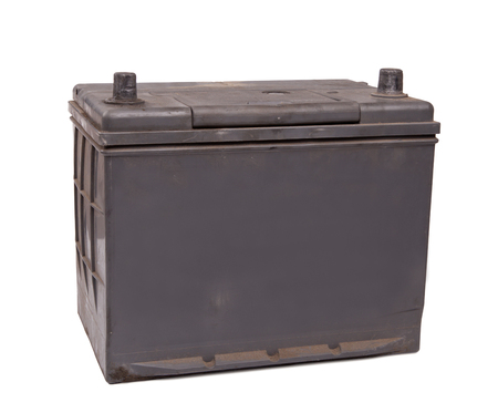 12v: old and dirty car battery. closeup on white