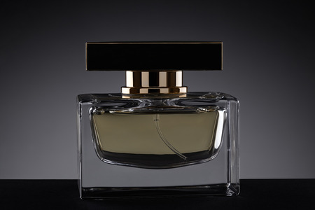 eau de perfume: jar of perfume on a dark gradient background, with beautiful reflections of light