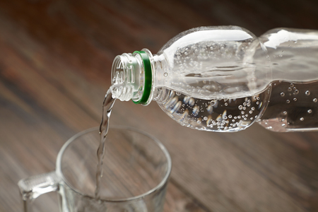 Mineral water pours into a glass, soda flows from a bottle