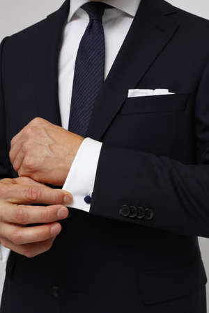 Close up of a man in suit. Man is holding cuff of suit