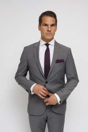 man with gray suit, white shirt, dark red tie and dark red handkerchief