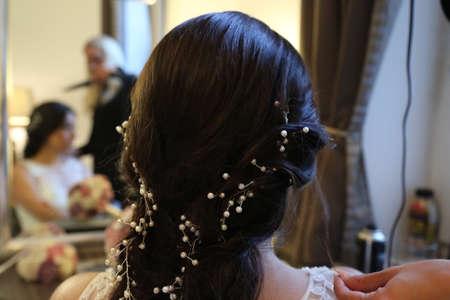 bride with dark hair is getting dressed