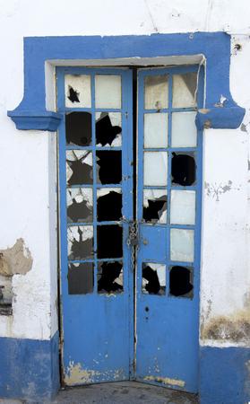 Blue door with broken glass rickety photo