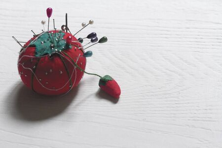 With Tomato pincer-shaped pins, thread and needle for sewing