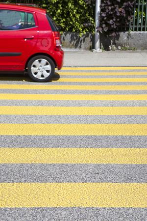 cross walk: Yellow cross walk on a Swiss street - passing red car, some motion blur