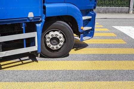 cross walk: Yellow cross walk on a Swiss street - turning blue truck, some motion blur