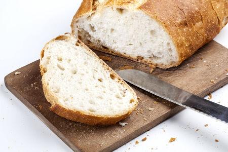 pain blanc: Tranche de pain blanc sur une planche de bois