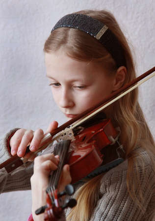 The girl plays a violin photo
