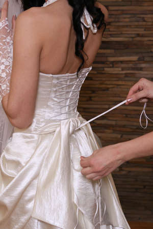 wedding party: Bride preparing for wedding dress