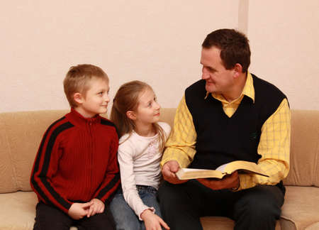 father reading a book to children at home photo