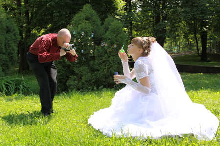 taking video: Bride takes a bubble on the grass and videographer Stock Photo