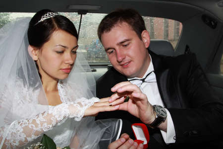 The groom dresses a ring to the bride in the car photo