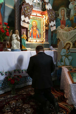 A man prays at the Greek-Catholic Church Stock Photo