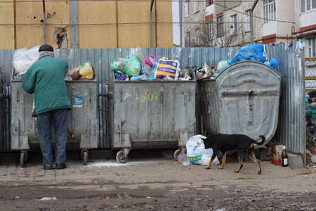 untidily: Ivano-Frankivsk, Ukraine - December 13, 2014:The person searches for something in garbage. Editorial