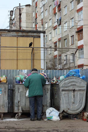 Ivano-Frankivsk, Ukraine - December 13, 2014:The person searches for something in garbage. Editorial