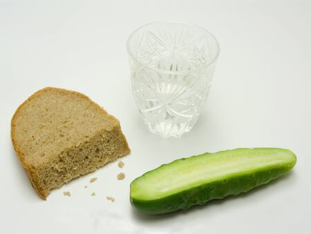 An isolated photo of a breakfast of a russian peasant consisting of vodka, bread and cucumber with salt