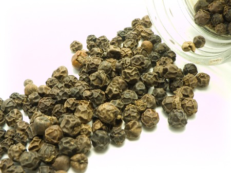 pungent: Ground spices in glass tableware and whole black pepper