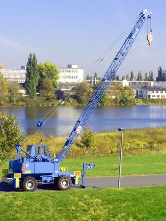 blue truck crane stands on the riverside with heaved up an arrow Фото со стока
