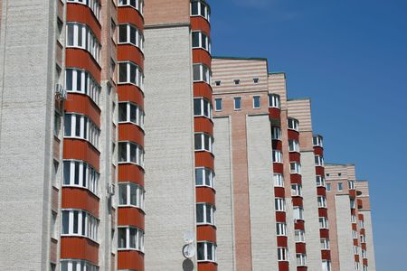 habitation: new brick multistoried building with red balconies on a background blue sky, social habitation