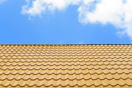 a roof is covered a yellow wavy metal on a background blue sky with white clouds Stock Photo - 3260963