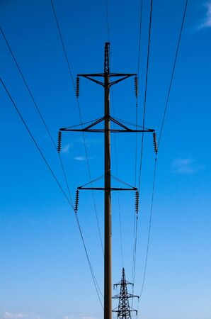 Electric power transmission on a background of the blue sky.
