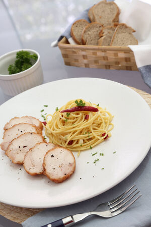 spaghetti with slicing meat and bread basket photo
