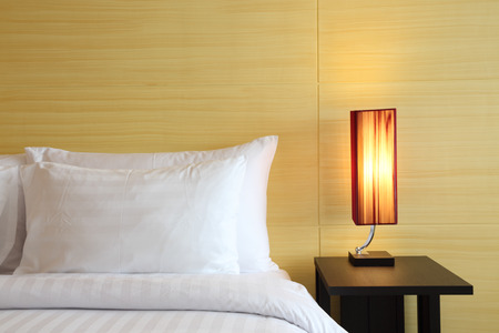 Boutique hotel bedroom setting with bed, pillows, nightstand and lamp