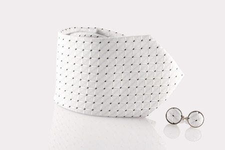 white tie with cuff links on white background