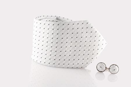 cuffs: white tie with cuff links on white background