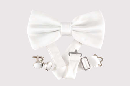cuff links: white bow tie  with cuff links on white background Stock Photo
