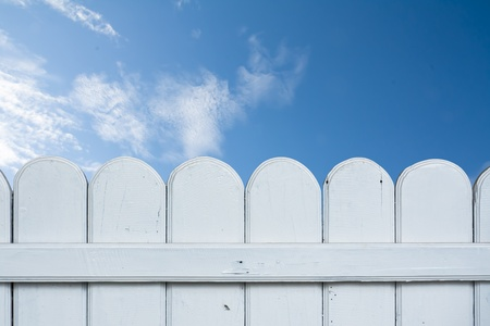 A white fence and blue sky.