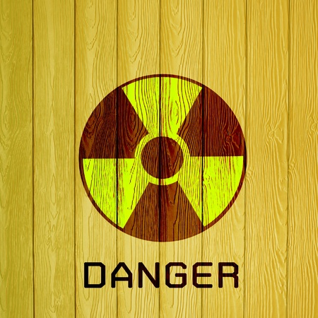 radioactivity warning symbol on wood background photo