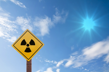 radioactivity warning symbol on blue sky background photo