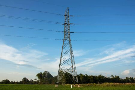 High voltage pylon in paddy with blue sky and clouds