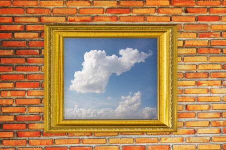 cloud picture and golden frame on old brick wall photo