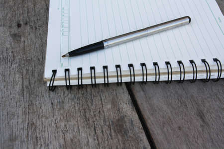 spiral notebook and pen on wooden desk photo