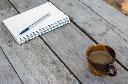 cup of coffee and spiral notebook on wood table photo