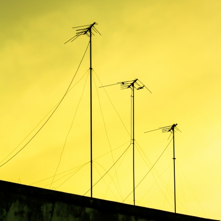 silhouettes of antennas with sunset photo