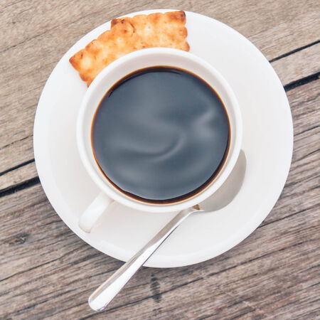 Cup of coffee with crackers on wooden photo