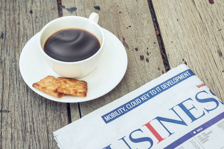 Cup of coffee with crackers and newspaper on wooden photo