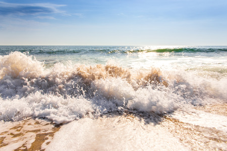 seawater: sand sea beach and blue sky after sunrise and splash of seawater with sea foam and waves