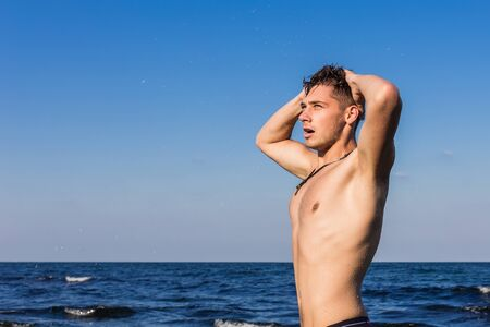 getting out: Attractive young man in the sea getting out of water with wet hair