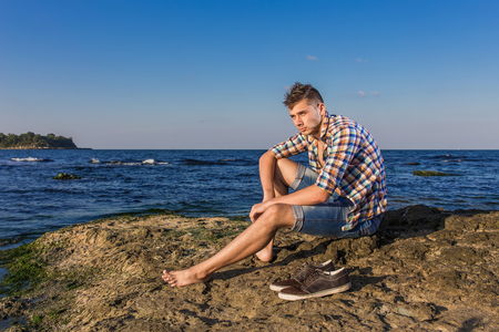 Attractive young fashion sexy man sitting on a rock near the sea water with shoes beside him