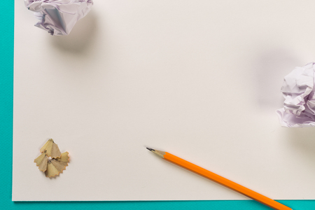 Pencils with sharpening shavings with white paper sheets on coloured backgroung, Office tool, rolled paper