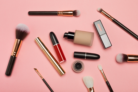 Professional makeup products with cosmetic beauty products, blushes, eye liner, eye lashes, brushes and tools on pink background